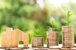 Baufinanzierung Betzdorf Hintergrundbild Münztürme mit Planze und Haus silhouette