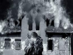 Wohngebäudeversicherung brennendes Haus mit verzweifelter Frau